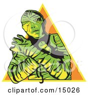 Mummy Wrapped Up With His Arms Crossed In Front Of Him And Cast In Green And Yellow Lighting Over An Orange Triangle