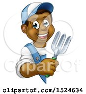 Happy Black Male Gardener Holding A Garden Fork Around A Sign