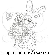 Black And White Female Bunny Rabbit Holding An Easter Cake