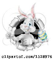 White Easter Bunny Rabbit Giving A Thumb Up And Holding An Egg While Emerging From A Hole