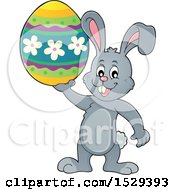 Clipart Of A Gray Bunny Rabbit Holding An Easter Egg Royalty Free Vector Illustration by visekart