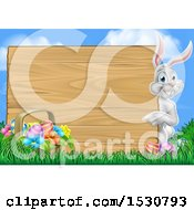 Happy White Easter Bunny Rabbit Pointing Around A Wood Sign Against Sky