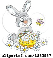 Clipart Of A Cute Gray Bunny Rabbit With An Easter Cake Royalty Free Vector Illustration