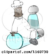 Black Male Chef Sitting On Top Of A Tipped Salt Shaker In Front Of A Pepper Shaker
