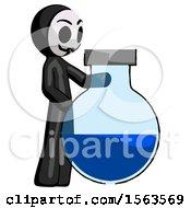 Black Little Anarchist Hacker Man Standing Beside Large Round Flask Or Beaker