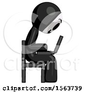 Black Little Anarchist Hacker Man Using Laptop Computer While Sitting In Chair View From Side