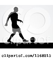 Black Silhouetted Male Soccer Player Over Gray