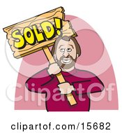 Happy Man In A Red Sweater Holding A Wooden Sold Sign After Selling A House