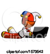 Orange Jester Joker Man Using Laptop Computer While Lying On Floor Side Angled View
