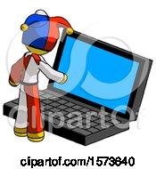 Yellow Jester Joker Man Using Large Laptop Computer