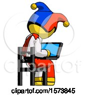 Yellow Jester Joker Man Using Laptop Computer While Sitting In Chair View From Back