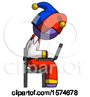 Purple Jester Joker Man Using Laptop Computer While Sitting In Chair View From Side