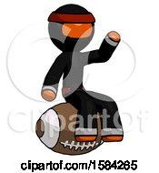 Orange Ninja Warrior Man Sitting On Giant Football