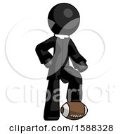 Black Clergy Man Standing With Foot On Football