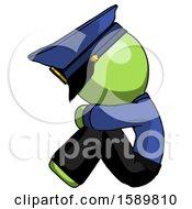 Green Police Man Sitting With Head Down Facing Sideways Left