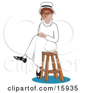 Pretty African American Woman In A Nurse Uniform Seated On A Stool With Her Legs Crossed