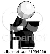 White Clergy Man Using Laptop Computer While Sitting In Chair Angled Right