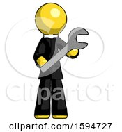 Yellow Clergy Man Holding Large Wrench With Both Hands
