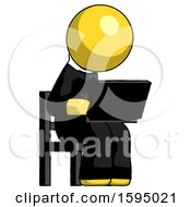 Yellow Clergy Man Using Laptop Computer While Sitting In Chair Angled Right
