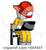 White Firefighter Fireman Man Using Laptop Computer While Sitting In Chair Angled Right