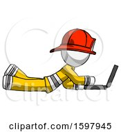 White Firefighter Fireman Man Using Laptop Computer While Lying On Floor Side View