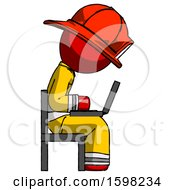Red Firefighter Fireman Man Using Laptop Computer While Sitting In Chair View From Side