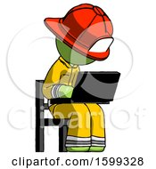 Green Firefighter Fireman Man Using Laptop Computer While Sitting In Chair Angled Right