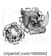 Clipart Of A Tough Rhino Monster Mascot Holding A Soccer Ball In One Clawed Paw And Breaking Through A Wall Royalty Free Vector Illustration by AtStockIllustration