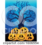 Group Of Halloween Jackolantern Pumpkins Under A Bare Tree On Blue