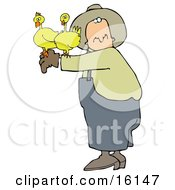 Male Farmer Holding Two Yellow Chickens On His Arm