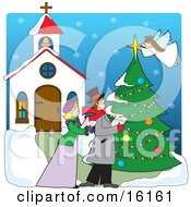 Woman And A Man Singing Christmas Carols In The Snow Outside Of A Church While An Angel Tops A Tree With A Star