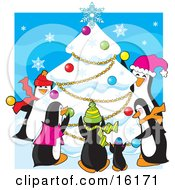 Group Of Happy Penguins Wearing Scarves And Hats While Decorating A Snow Flocked Christmas Tree With Ornaments Garlands And A Snowflake At The Top