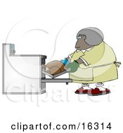 Middleaged African American Woman Wearing Mis-Matched Oven Mits And Putting A Turkey In The Oven While Cooking For Thanksgiving Or Christmas Dinner