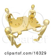 Team Of Four Golden People Holding Up Connected Pieces To A Gold Puzzle Symbolizing Excellent Teamwork Success And Link Exchanging