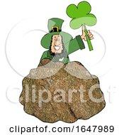 Cartoon St Patricks Day Leprechaun Holding Up A Shamrock Behind A Rock