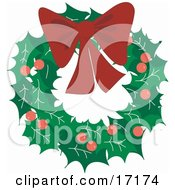 Decorative Christmas Wreath Made Of Holly And Berries Topped With A Red Bow