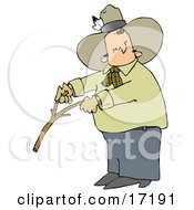 Caucasian Cowboy With A Feather In His Hat Looking Back Over His Shoulder While Handling A Stick While Water Witching Or Dowsing