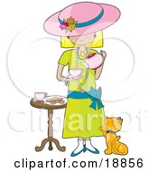 Cute Little Blond Caucasian Girl Dressed In Her Mothers Clothes And Pouring A Cup Of Tea Into A Cup While A Marmalade Cat Looks Up At Her Waiting For A Treat