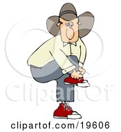 White Cowboy Guy In A Hat Lifting His Knee Up To Tie His Shoe Laces While Standing