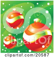 Three Orange Red And Gold Christmas Bauble Ornaments Over A Green Snowy Background