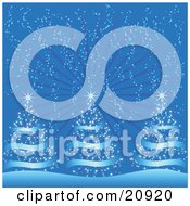 Clipart Illustration Of Three Blue Christmas Trees With Shining Stars On Top Being Snowed On On A Cold Wintry Night