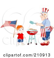 Patriotic Boy Waving An American Flag Near His Dad As He Barbecues Food For A Fourth Of July Picnic