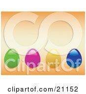 Green Pink Yellow And Blue Colored Easter Eggs In A Row Over A Pale Orange Background