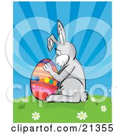 Clipart Illustration Of A Lonely Easter Bunny Hugging A Colorful Easter Egg On Top Of A Hill With Spring Flowers Against A Blue Sky