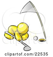 Yellow Man Down On The Ground Trying To Blow A Golf Ball Into The Hole