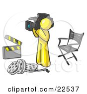 Clipart Illustration Of A Yellow Man Filming A Movie Scene With A Video Camera In A Studio
