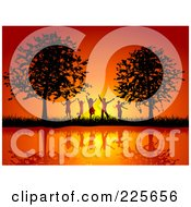 Group Of Silhouetted Happy Children Against An Orange Sunset Between Trees On A Waterfront