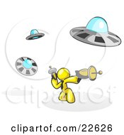Clipart Illustration Of A Yellow Man Fighting Off UFOs With Weapons by Leo Blanchette