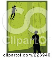 Pair Of Rock Climbers Scaling A Green Climbing Wall