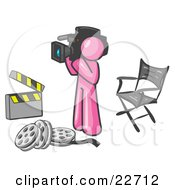 Clipart Illustration Of A Pink Man Filming A Movie Scene With A Video Camera In A Studio